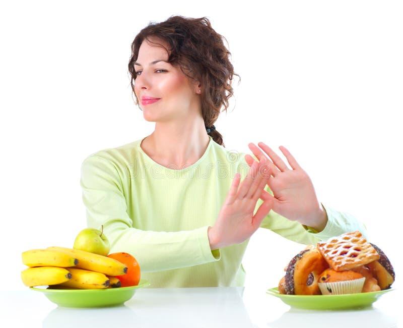 Dieta. Mulher que escolhe entre frutas e doces foto de stock royalty free