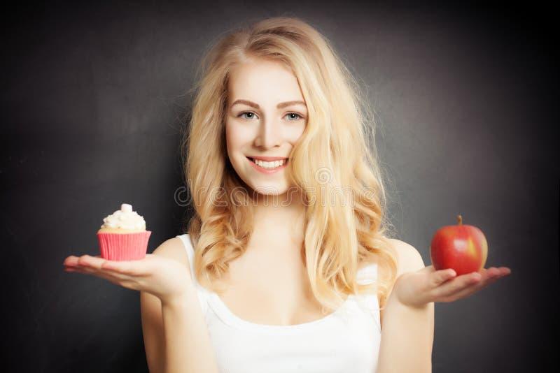 Dieta Mulher saudável que guarda Apple e o bolo imagens de stock