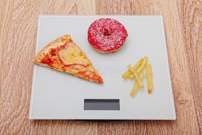Dieta O conceito da comida lixo no peso Estilo de vida saudável Fundo de madeira foto de stock