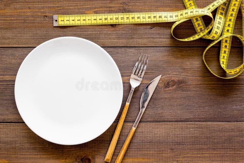 Dieta para el concepto de la pérdida de peso Nutrición apropiada Hambre médica Placa vacía con la bifurcación y cuchillo cerca de fotos de archivo
