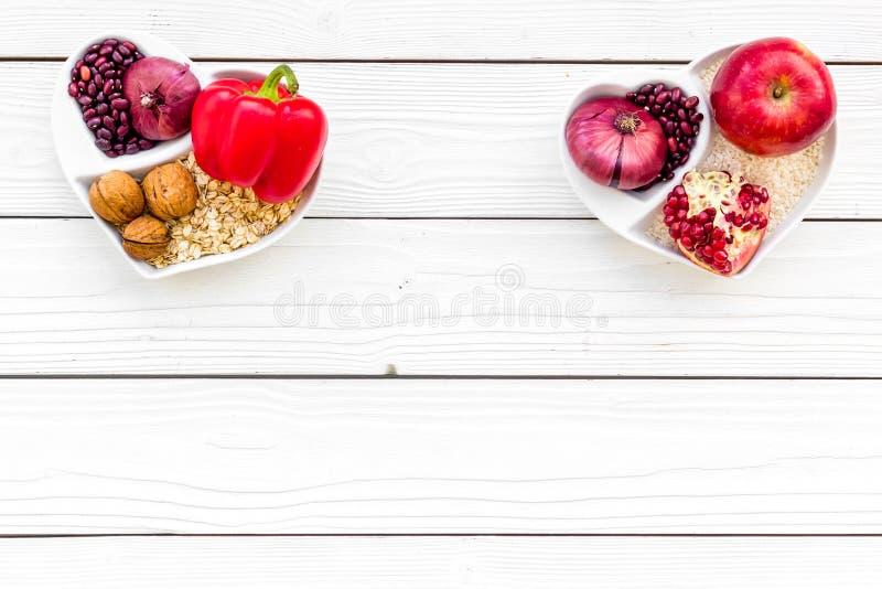 Dieta para el corazón sano Comida con los antioxidantes Verduras, frutas, nueces en cuenco en forma de corazón en el fondo de mad imagen de archivo