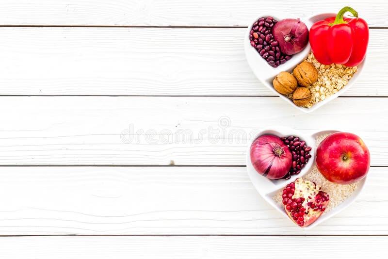 Dieta para el corazón sano Comida con los antioxidantes Verduras, frutas, nueces en cuenco en forma de corazón en el fondo de mad foto de archivo