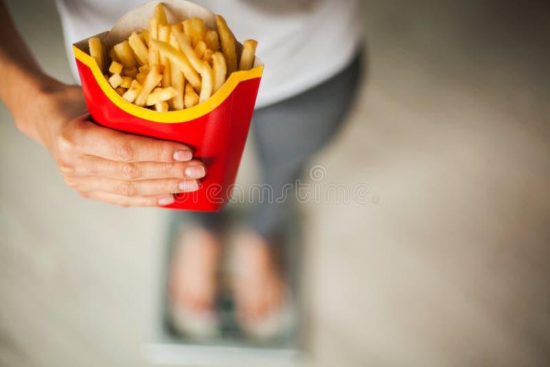 Dieta Peso corporal de medição da mulher na escala de peso que guarda a comida lixo insalubre Perda de peso obesity Vista superio imagens de stock royalty free