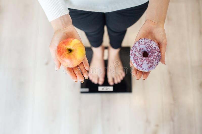 Dieta Peso corporal de medição da mulher na escala de peso que guarda a filhós e a maçã Os doces são comida lixo insalubre dietin imagem de stock