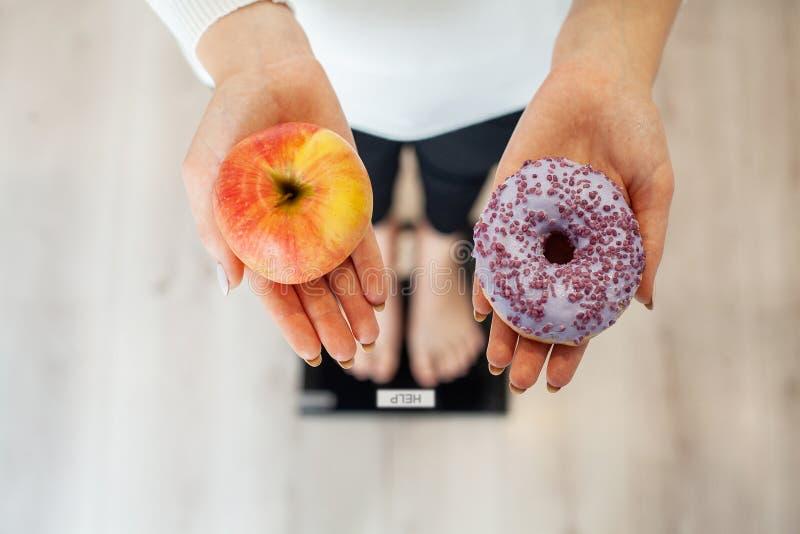 Dieta Peso corporal de medição da mulher na escala de peso que guarda a filhós e a maçã Os doces são comida lixo insalubre dietin fotos de stock