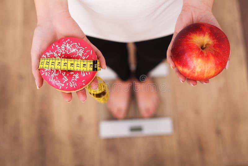 Dieta Peso corporal de medição da mulher na escala de peso que guarda a filhós e a maçã Os doces são comida lixo insalubre Fazend imagens de stock