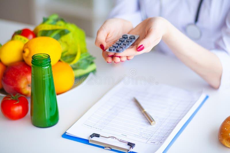 Dieta Pillole della tenuta del dottore Nutritionist nel suo ufficio Concetto di n fotografia stock