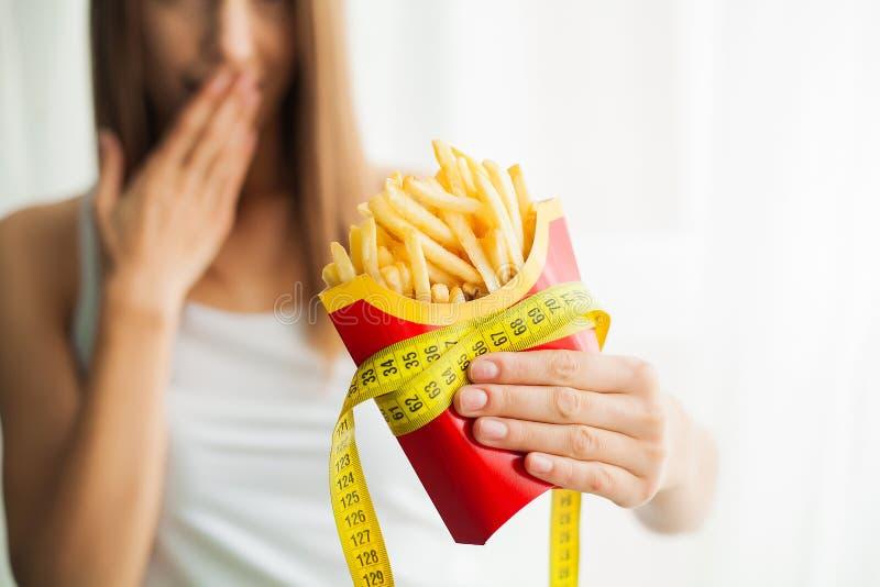 Dieta Posição da mulher em escalas e guardar microplaquetas de batata O conceito de comer saud?vel Estilo de vida saud?vel Dieta foto de stock