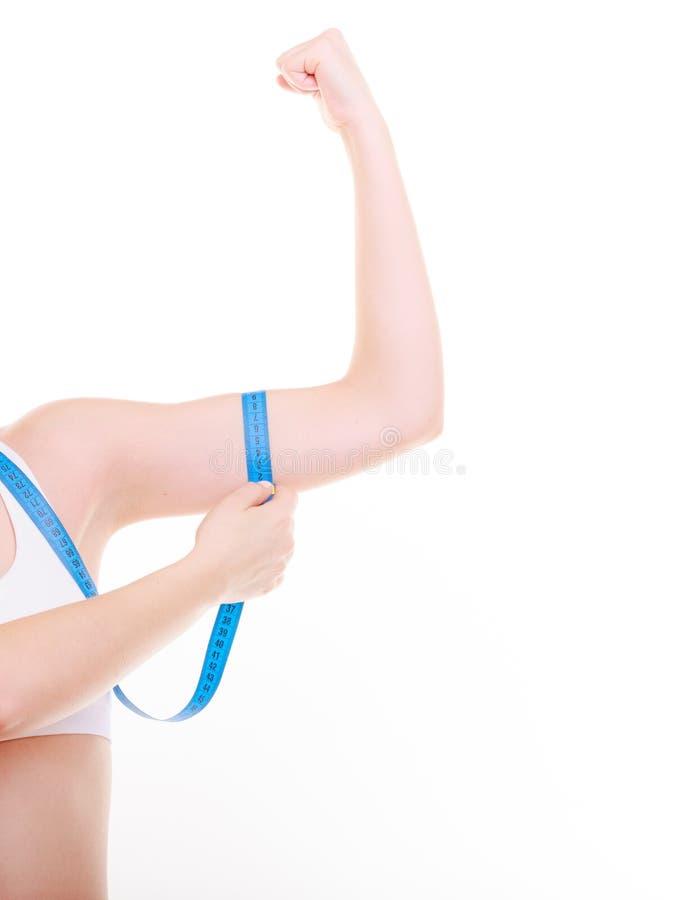 Dieta Ragazza adatta della donna di forma fisica con la misurazione di nastro di misura il suo bicipite immagine stock libera da diritti