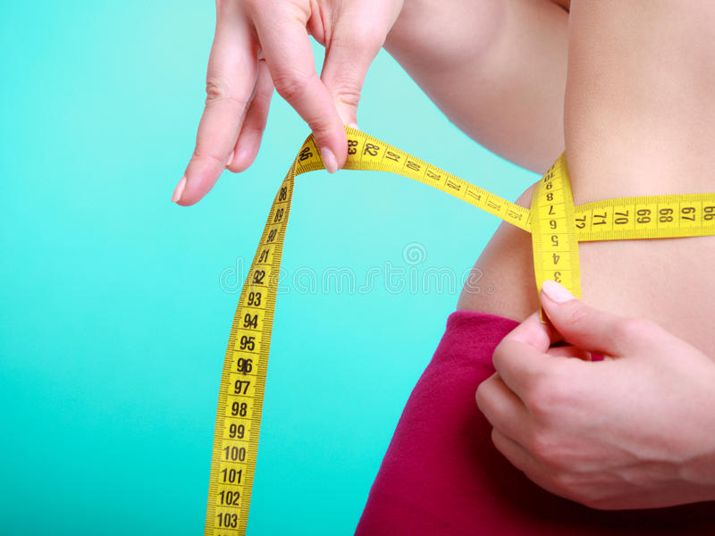 Dieta. Ragazza adatta della donna di forma fisica con la misurazione di nastro di misura la sua vita fotografie stock