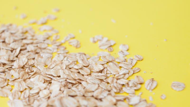Dieta sana, el concepto Harina de avena del grano en un fondo amarillo Las escamas de la avena dispersaron fotos de archivo
