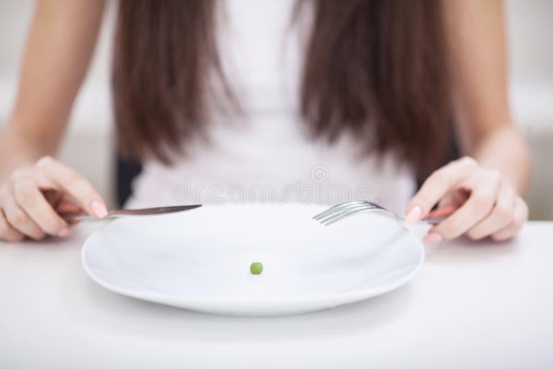 Dieta Soffrendo dall'anoressia Immagine potata della ragazza che prova alla p fotografia stock