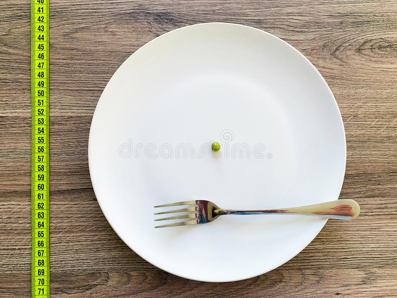 Dieta Soffrendo dall'anoressia Pisello potato di immagine sul piatto bianco, con la forcella e la misurazione fotografia stock libera da diritti