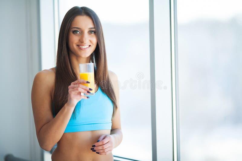 Dieta Succo d'arancia bevente sorridente felice della giovane donna immagini stock