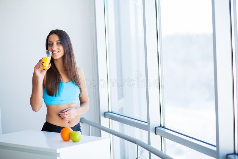 Dieta Succo d'arancia bevente sorridente felice della giovane donna fotografia stock
