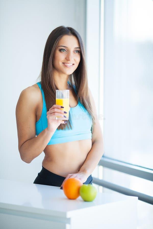 Dieta Succo d'arancia bevente sorridente felice della giovane donna fotografia stock libera da diritti