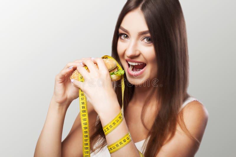 dieta Szkodliwy i pożytecznie jedzenie Młoda dziewczyna robi wyborowemu eithe obrazy royalty free