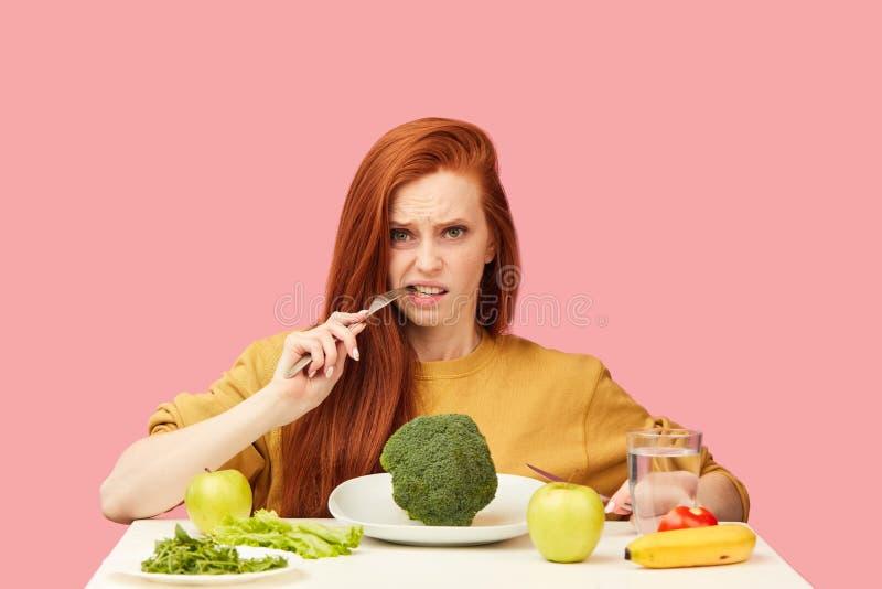 Dieta vegetal Mujer embotada triste que sostiene el bróculi en la bifurcación mientras que hace la mueca fotografía de archivo libre de regalías