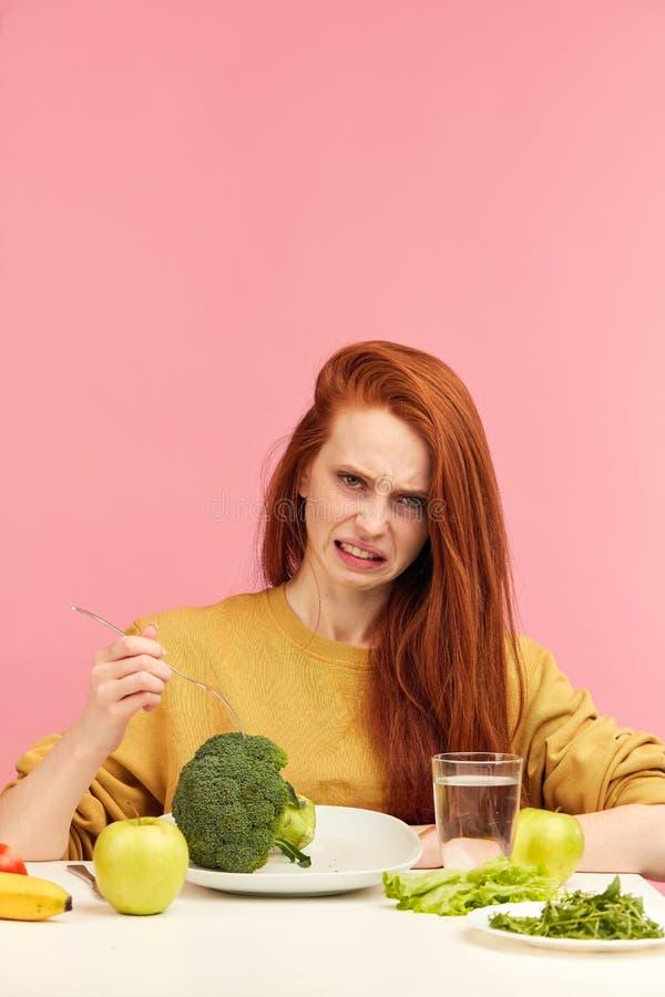 Dieta vegetal Mujer embotada triste que sostiene el br?culi en la bifurcaci?n mientras que hace la mueca imágenes de archivo libres de regalías