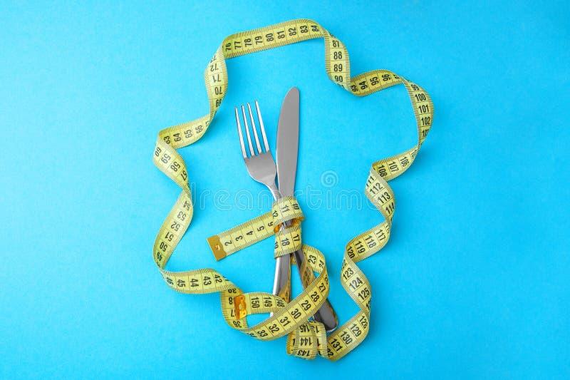 Dieta vegetal para la pérdida de peso La bifurcación y el cuchillo se envuelven en cinta métrica amarilla en azul fotografía de archivo libre de regalías