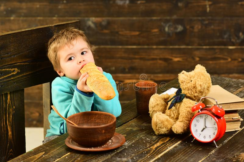 Dieta y comida Adiete, niño pequeño comen el baguette francés en la tabla La dieta cura más que doctores Dieta sana para el niño fotos de archivo