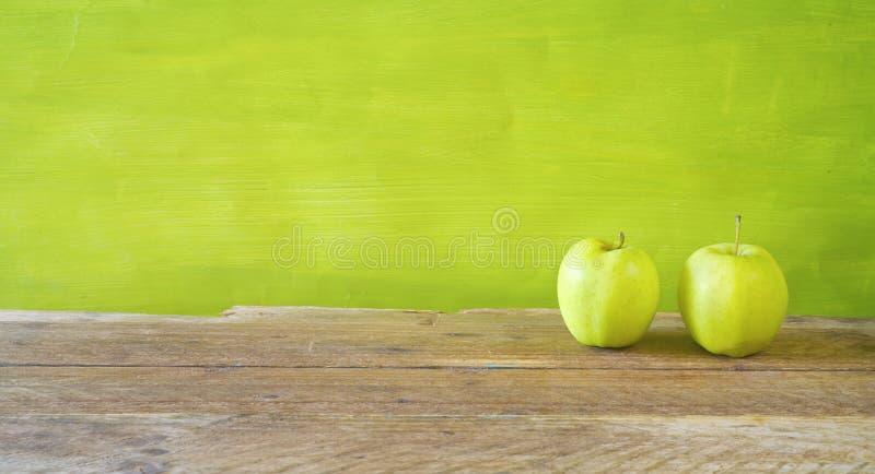 Dieta y concepto sano de la comida con dos manzanas verdes en el fondo verde, mofa panorámica para arriba, espacio de la copia li imagenes de archivo