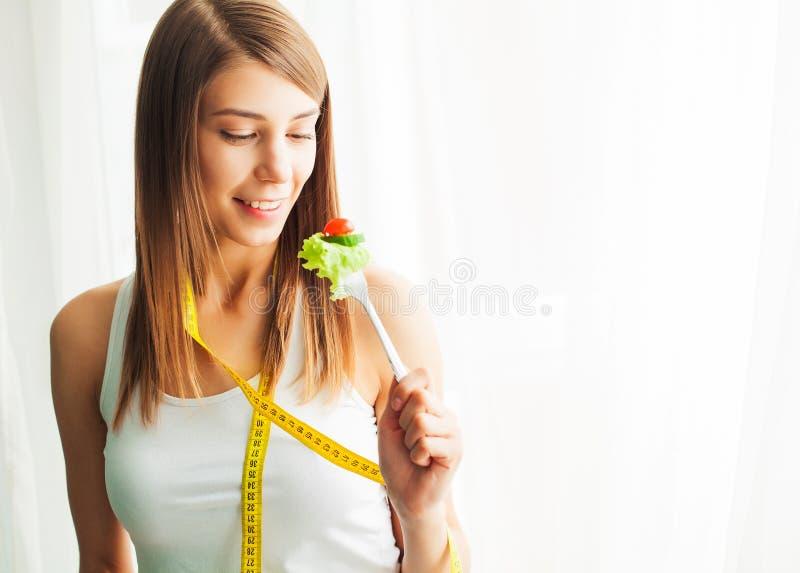 Dieta y consumici?n sana Mujer joven que come la ensalada sana despu?s de entrenamiento imagen de archivo libre de regalías