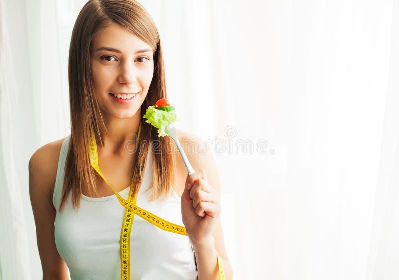 Dieta y consumici?n sana Mujer joven que come la ensalada sana despu?s de entrenamiento imágenes de archivo libres de regalías