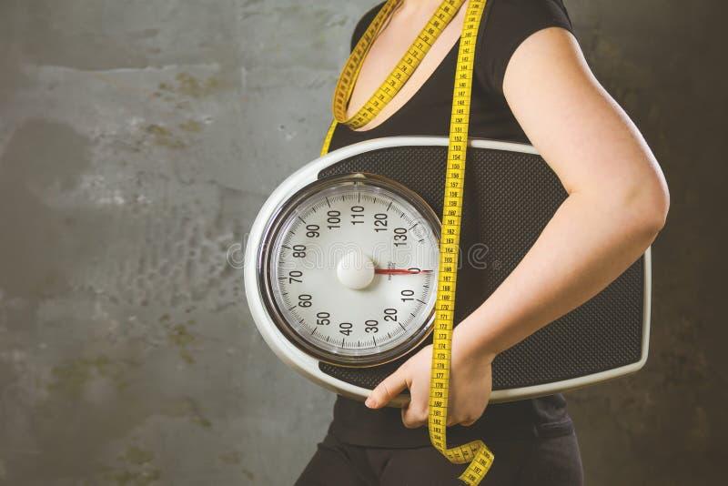Dieta y peso - mujer joven con una escala imagenes de archivo