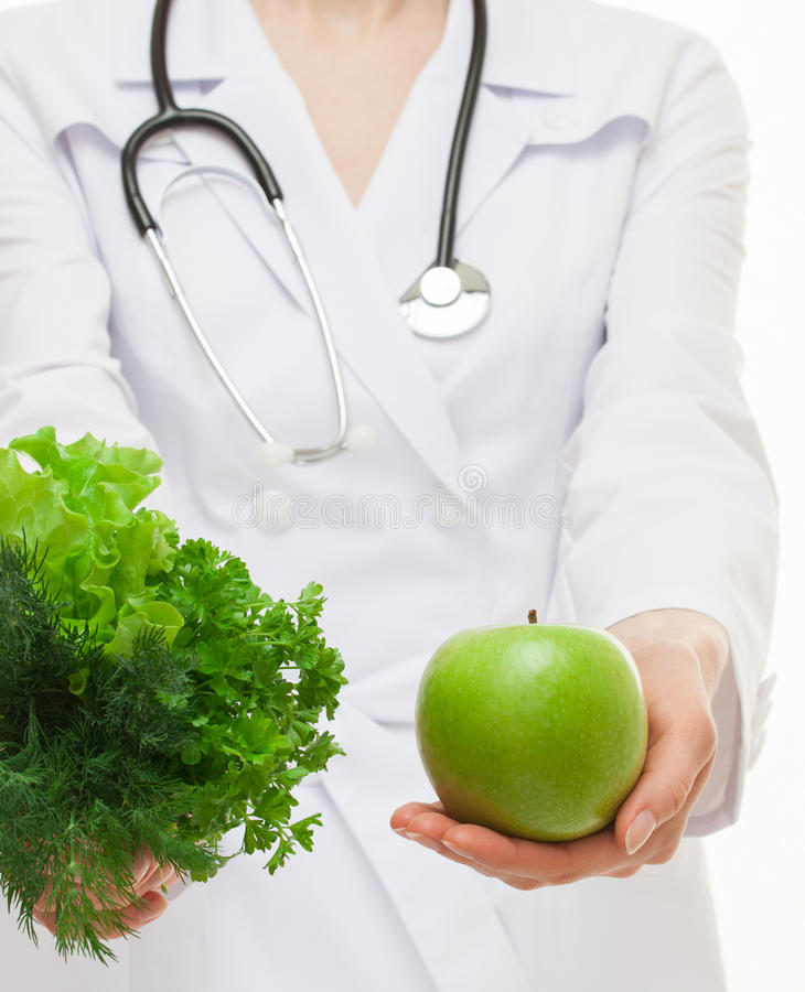 Dietarian proposing fresh greens and a green apple for you. White background royalty free stock image