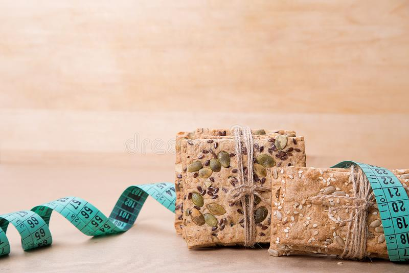 Dietary bread and measuring tape. Diet and health. Dietary bread and measuring tape on craft paper. Diet and health concept royalty free stock photo
