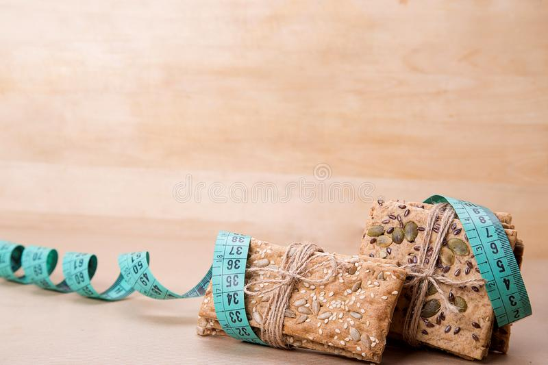 Dietary bread and measuring tape. Diet and health. Dietary bread and measuring tape on craft paper. Diet and health concept royalty free stock photography
