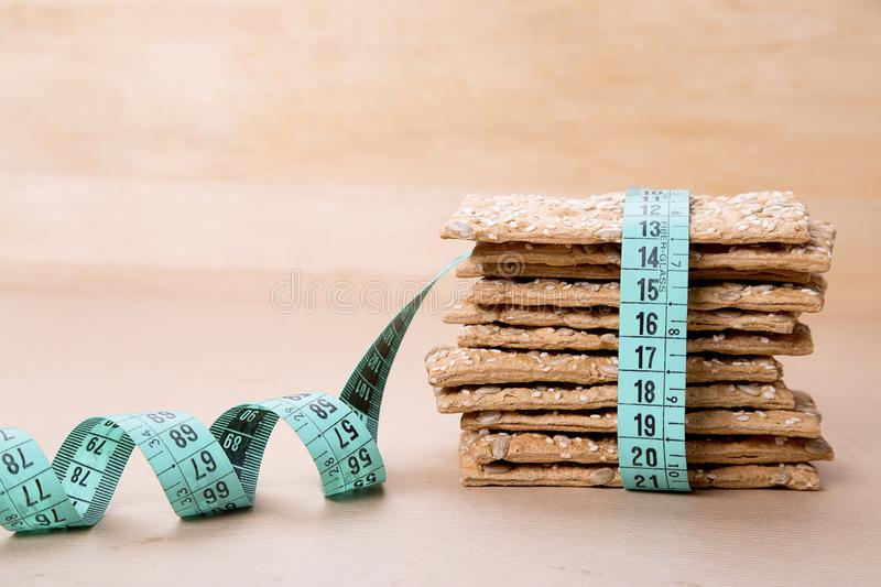 Dietary bread and measuring tape. Diet and health. Dietary bread and measuring tape on craft paper. Diet and health concept stock image