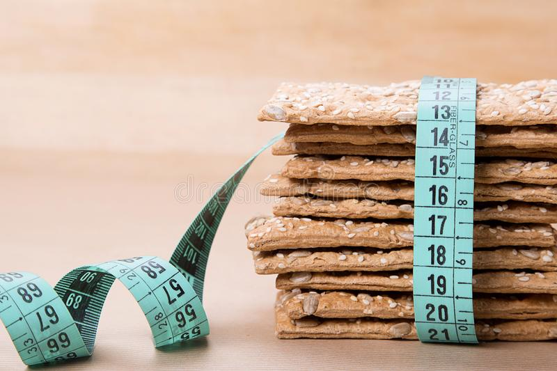 Dietary bread and measuring tape. Diet and health. Dietary bread and measuring tape on craft paper. Diet and health concept royalty free stock photos