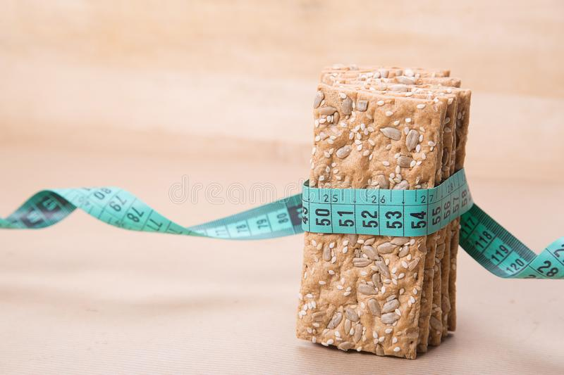 Dietary bread and measuring tape. Diet and health. Dietary bread and measuring tape on craft paper. Diet and health concept royalty free stock image