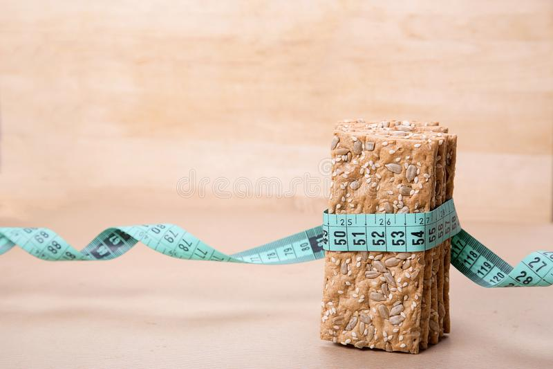 Dietary bread and measuring tape. Diet and health. Dietary bread and measuring tape on craft paper. Diet and health concept royalty free stock images