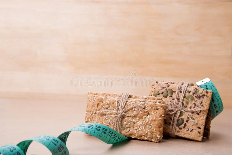 Dietary bread and measuring tape. Diet and health. Dietary bread and measuring tape on craft paper. Diet and health concept stock images