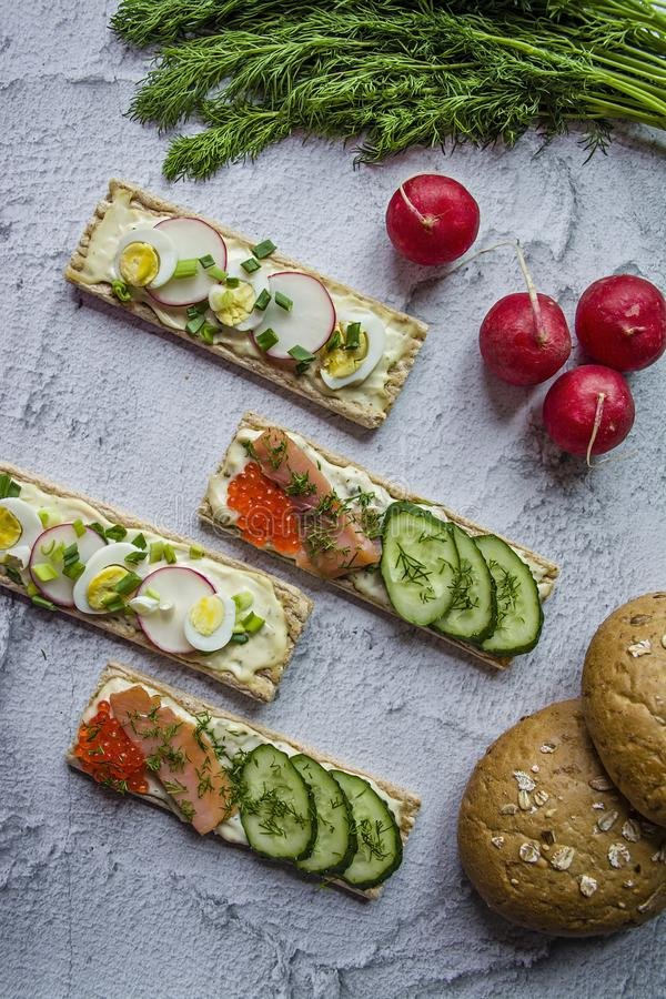 Dietary bread with quail egg and radish, as well as with caviar and cucumbers. Vegetarian sandwiches. Light background. Close-up royalty free stock photos