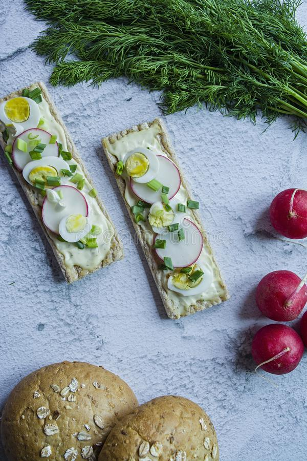 Dietary bread with quail egg, radish and melted cheese. Vegetarian sandwiches. Light background Close-up.  stock photos