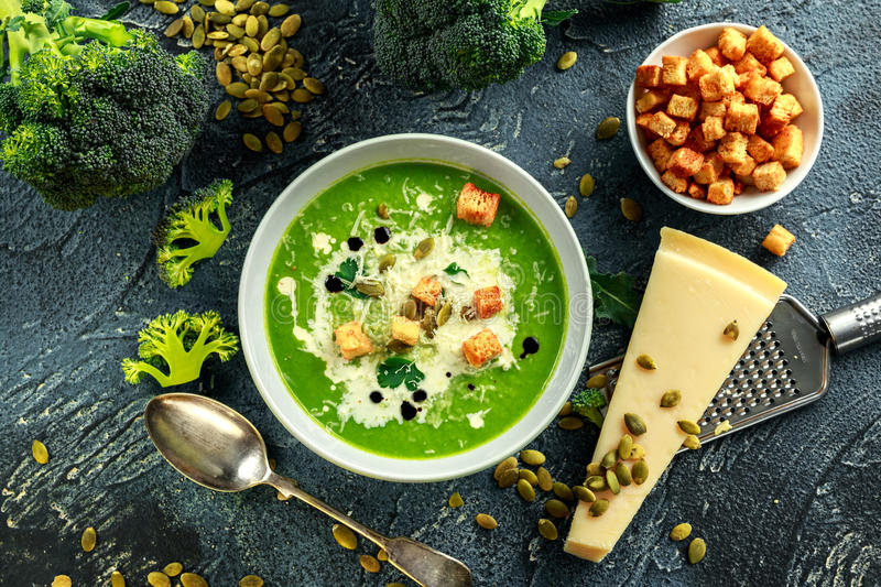 Dietary Broccoli smooth cream soup with sprinkle of sunflower seeds, parsley leaves and croutons on stone table. royalty free stock photo