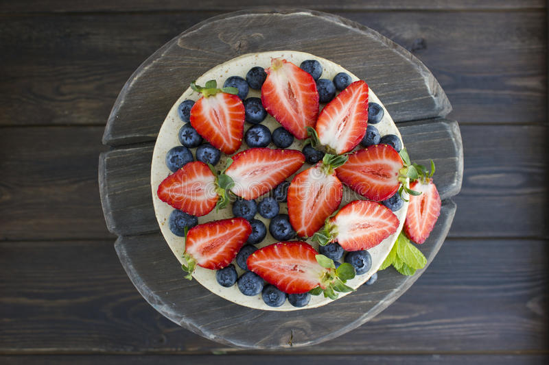 Dietary cake with berries on a wooden tray. Delicious, useful. royalty free stock photo
