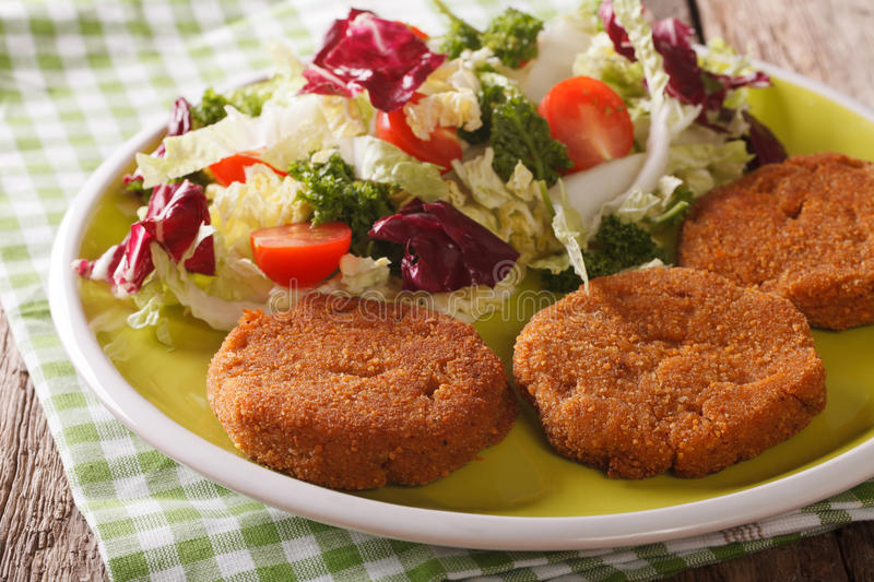 Dietary carrot cutlets and salad of chicory, cabbage and tomatoes close-up. horizontal stock photo