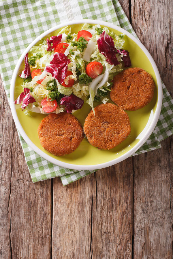 Dietary carrot cutlets and salad of chicory, cabbage and tomatoes close-up. vertical top view royalty free stock photo