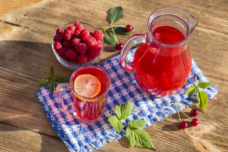 Dietary detox drink with lemon juice, red strawberry, cherry and raspberry in clear water with ice. Dietary detox drink with lemon juice, red cherry, strawberry royalty free stock photography
