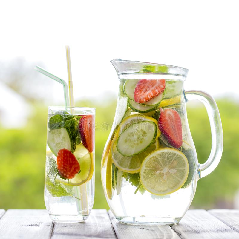 Dietary detox drink with yellow lemon juice, red strawberry, green cucumber and mint leaves in clear water with ice on the wooden royalty free stock photos
