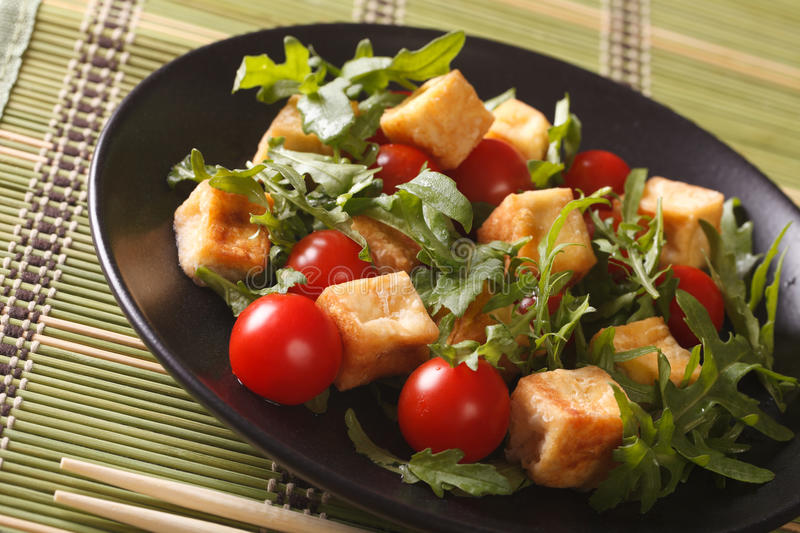 Dietary food: fried tofu with tomatoes and fresh arugula close-up. Horizontal royalty free stock photography