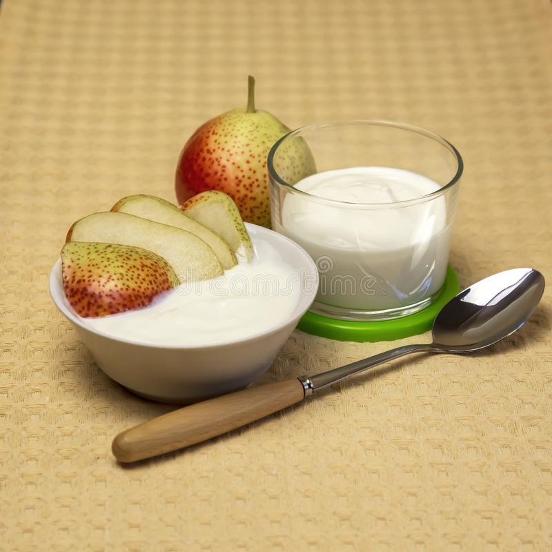 Dietary food. Fruit dairy product. Yogurt with fresh red pear. royalty free stock images