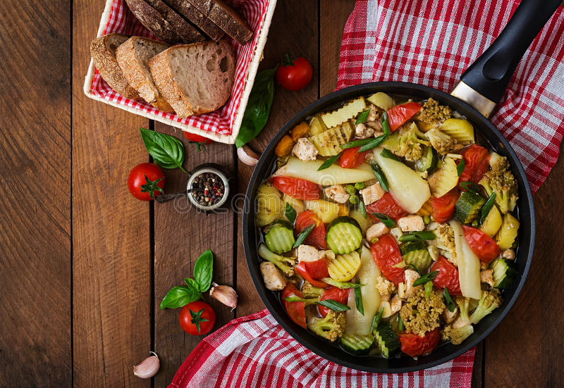 Dietary menu. Steamed vegetables with chicken fillet in pan on the wooden background. royalty free stock image