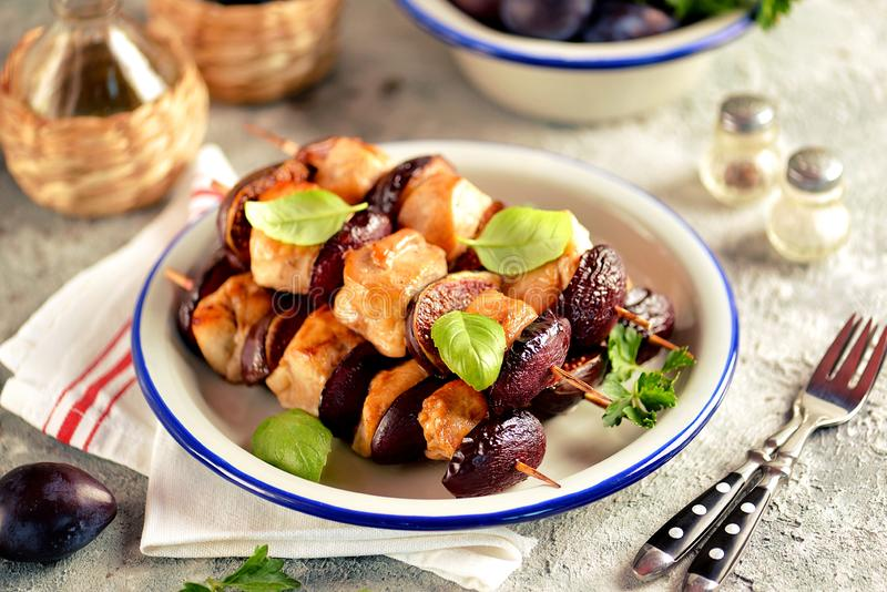 Dietary organic chicken kebab with plums and figs on wooden skewers. royalty free stock photography