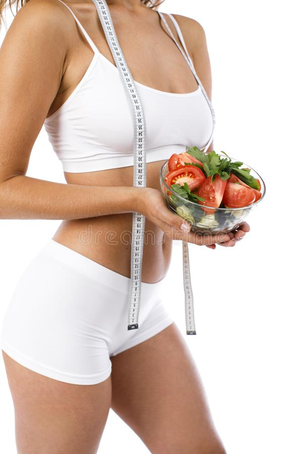 Dietary salad and slender female figure royalty free stock photo